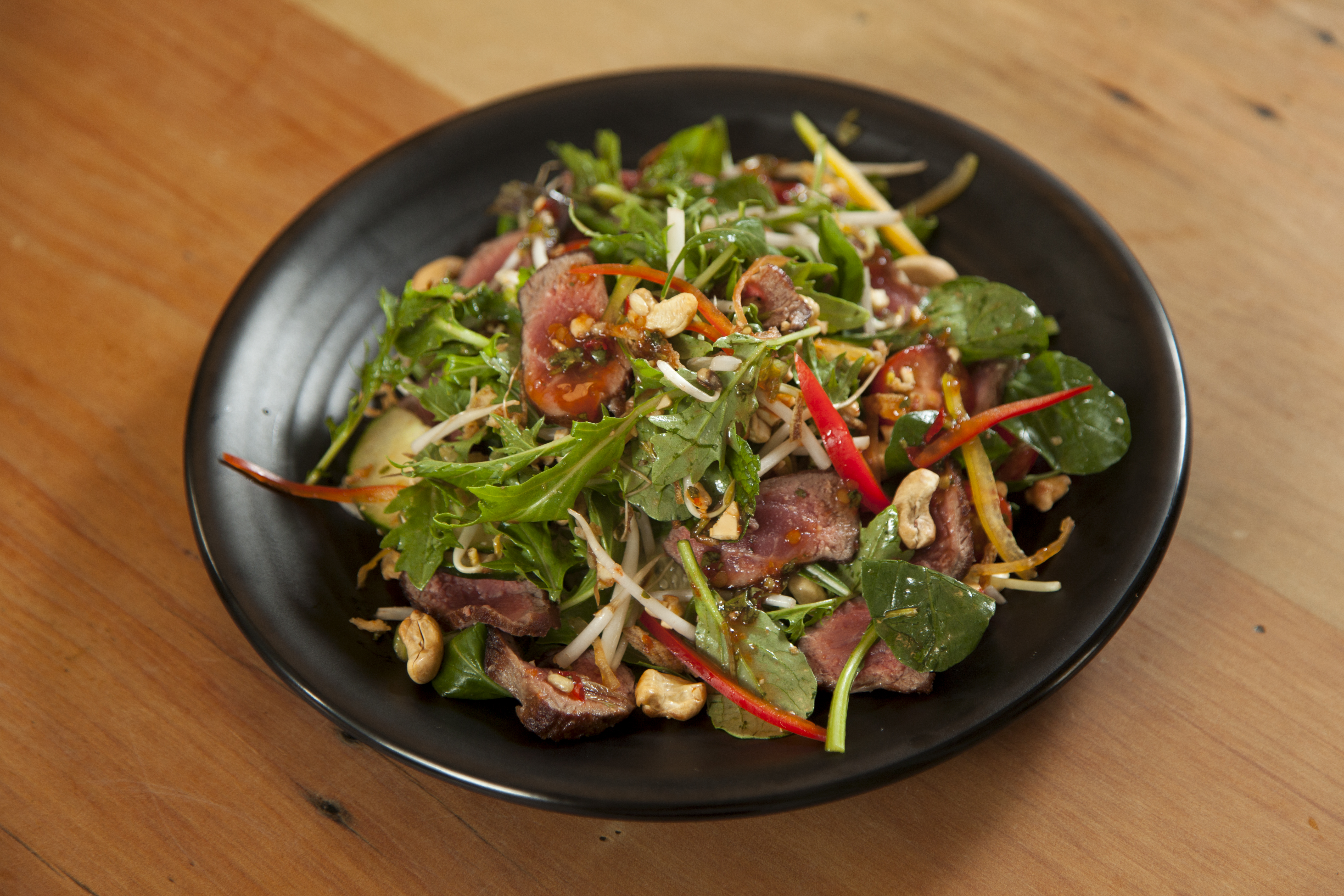 Succulent strips of beef tossed through an aromatic salad with a delicious traditional Thai chilli lime dressing, topped with toasted cashews [GF]